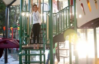 girl hanging on playground bars