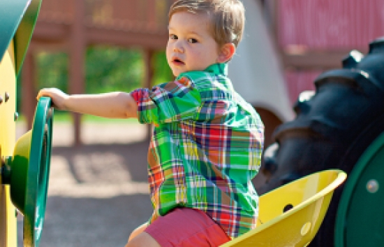 child playing on tractor playground slide